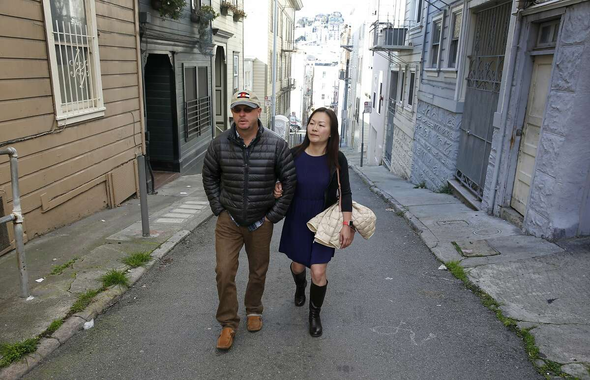 Tom Payne and Michelle Huang walk through an alley near the building on Vallejo Street where they own three TIC units in San Francisco, Calif. on Thursday, Feb. 4, 2016. They are embroiled in a feud with the owner of one of the other units who rented one of theirs through Airbnb and is now claiming residency asserting tenants rights.