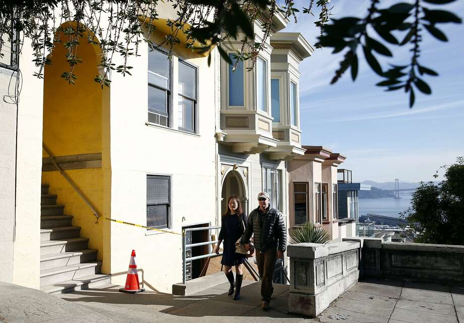 Michelle Huang and Tom Payne walk past the building on Vallejo Street where they own three TIC units in San Francisco, Calif. on Thursday, Feb. 4, 2016. They are embroiled in a feud with the owner of one of the other units who rented one of theirs through Airbnb and is now claiming residency asserting tenants rights. Photo: Paul Chinn, The Chronicle