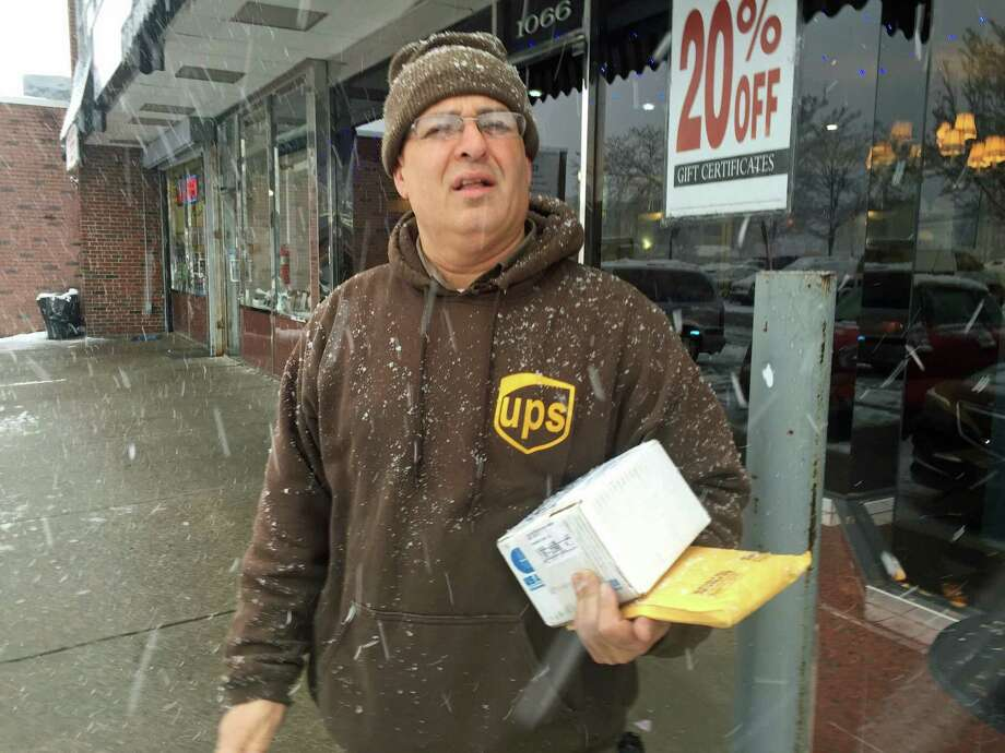 Ramon Morales takes extra care driving his UPS truck when it snows like it did Friday. Morales said he typically makes 160 to 180 deliveres each day, including his stop here at the Springdale Shopping Center. Photo: Brian Koonz / Hearst Connecticut Media / Stamford Advocate