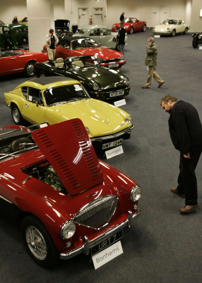 A man views a 1956 Austin-Healey 100 Roadster car prior to an auction of motor cars, vintage motorcycles and automobilia, in central London, Monday, Dec. 5, 2005. The car was sold for 22,500 pounds ($US 39,231) plus buyers premium and taxes. (AP Photo/ Lefteris Pitarakis) Photo: LEFTERIS PITARAKIS / AP