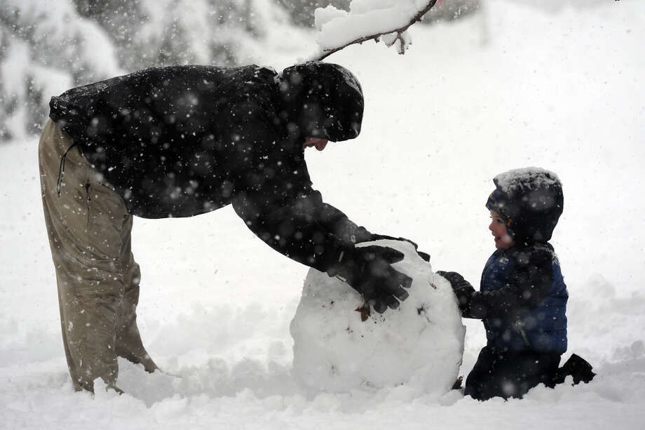 Todd Feineigle and his son Bennett, 3, work to roll snow as they build a snowman in their Stratford, Conn. homm Feb. 5, 2016. Photo: Ned Gerard, Hearst Connecticut Media / Connecticut Post