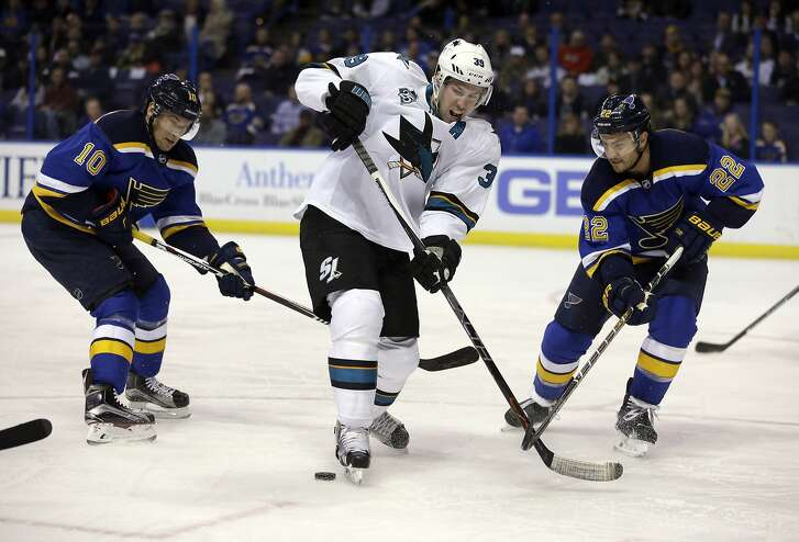 San Jose Sharks' Logan Couture, center, skates past the puck as St. Louis Blues' Scottie Upshall, left, and Kevin Shattenkirk defend during the first period of an NHL hockey game Thursday, Feb. 4, 2016, in St. Louis. (AP Photo/Jeff Roberson)