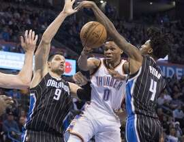 Orlando Magic center Nikola Vucevic (9) and Orlando Magic guard Elfrid Payton (4) force Oklahoma City Thunder guard Russell Westbrook (0) to pass the ball off during the second half of a NBA basketball game in Oklahoma City, Wednesday, Feb. 3, 2016. The Thunder won 117-114.  (AP Photo/J Pat Carter)