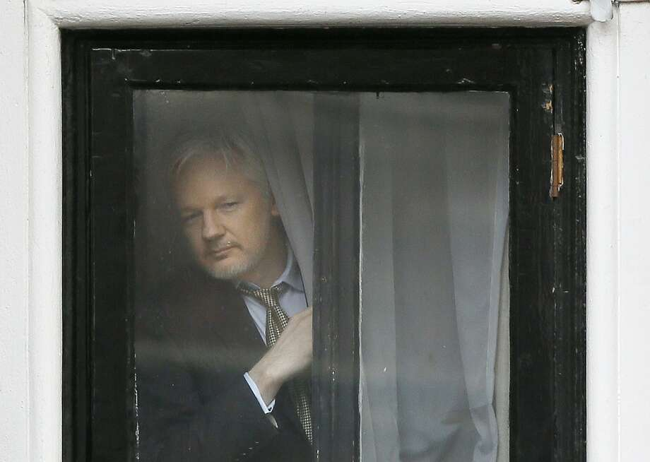 WikiLeaks' Julian Assange looks out a window before speaking on the balcony of the Ecuadoran Embassy in London, which he entered voluntarily in 2012. Photo: Kirsty Wigglesworth, Associated Press