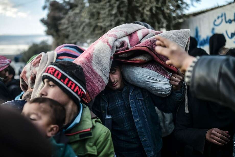 A man carries belongings as Syrians fleeing Aleppo wait near a Turkish crossing gate. Almost 40,000 civilians have fled a government offensive, and Turkey is bracing for a wave of refugees. Photo: Bulent Kilic, AFP / Getty Images