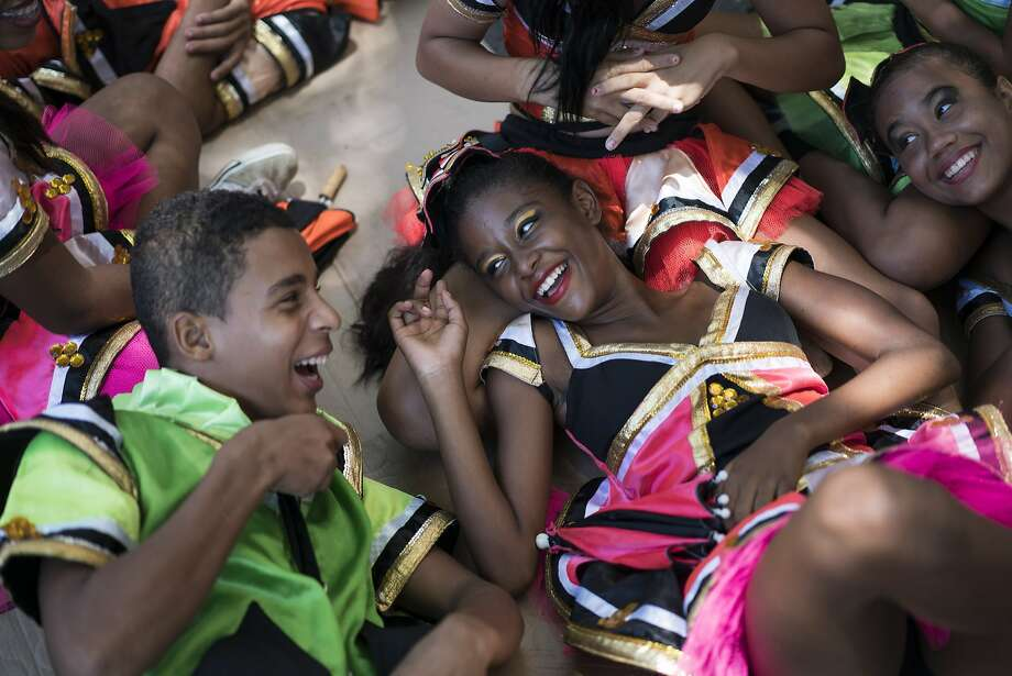 "Young revelers joke with each other as they lay on the shade during the ""Burial of the Mosquito"" carnival block parade in Olinda, Pernambuco state. Photo: Felipe Dana, Associated Press"