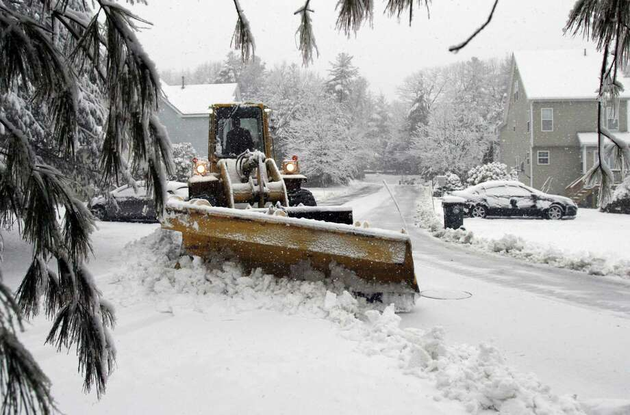 A plow driver clears snow from a road Friday, Feb. 5, 2016, in Marlborough, Mass. What started off as rain Friday morning quickly turned to sticky, heavy snow. Many school districts in the region closed for the day, including in some in Massachusetts, New Hampshire and Rhode Island. (AP Photo/Bill Sikes) ORG XMIT: MAWS101 Photo: Bill Sikes / AP