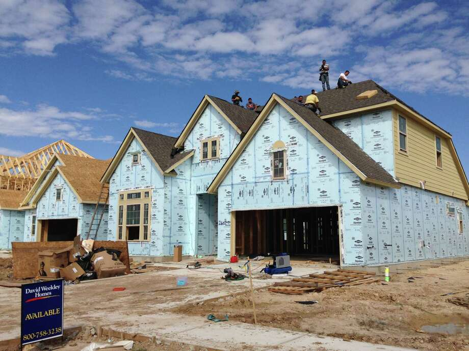 Construction workers build a house in Pomona near Texas 288 and County Road 101 in Manvel. David Weekley Homes is one of the builders along with Coventry Homes, Plantation Homes and Trendmaker Homes. Photo: Katherine Feser