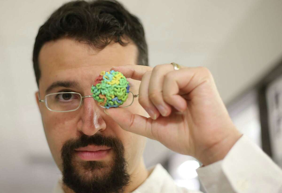 Erez Aiden, who is in charge of the center for genomics at Baylor College of Medicine holds a debunked model on Wednesday, Dec. 23, 2015, in Houston. ( Elizabeth Conley / Houston Chronicle )