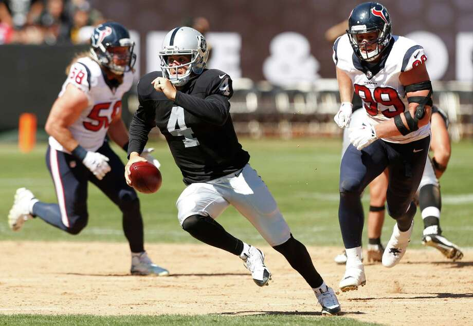 Oakland Raiders quarterback Derek Carr (4) is chased out of the pocket by Houston Texans outside linebacker Brooks Reed (58) and defensive end J.J. Watt (99) during the second quarter of an NFL football game at O.co Coliseum on Sunday, Sept. 14, 2014, in Oakland, Calif. Photo: Brett Coomer, Staff / © 2014  Houston Chronicle