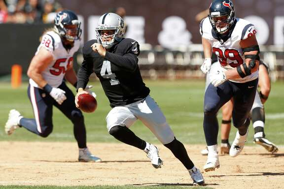 Oakland Raiders quarterback Derek Carr (4) is chased out of the pocket by Houston Texans outside linebacker Brooks Reed (58) and defensive end J.J. Watt (99) during the second quarter of an NFL football game at O.co Coliseum on Sunday, Sept. 14, 2014, in Oakland, Calif.