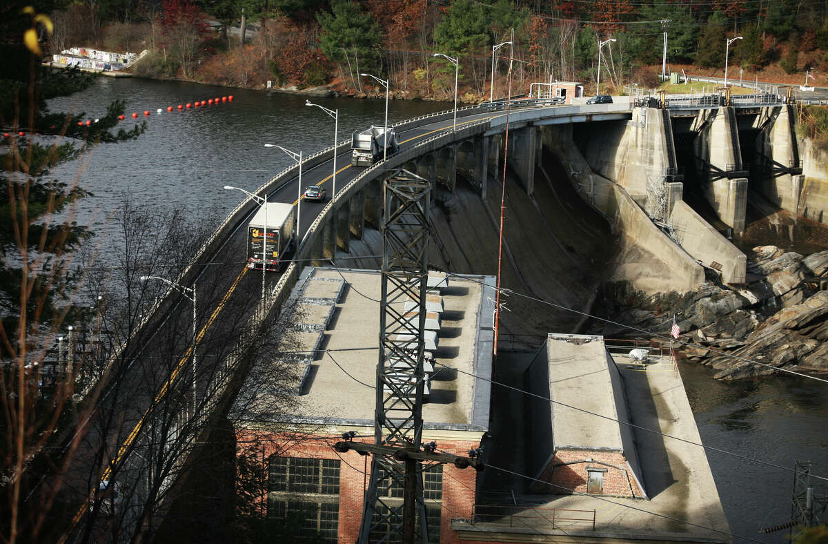 Cars and trucks make their way across the narrow roadway atop the Stevenson Dam in Monroe.