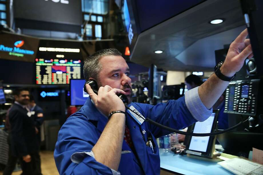 Traders on the floor of the New York Stock Exchange watch as markets drop despite an encouraging jobs report. Photo: Spencer Platt, Getty Images