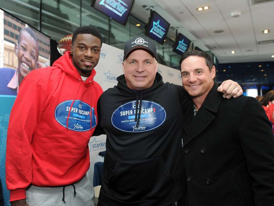 IMAGE DISTRIBUTED FOR STARKEY HEARING FOUNDATION - Garth Brooks, center, poses with A. J. Green, left, of the Cincinnati Bengals, and Jay Feely, of the Arizona Cardinals, at the Starkey Hearing Foundation's hearing mission, Saturday, Feb. 1, 2014, at Yankee Stadium in New York. (Photo by Diane Bondareff/Invision for Starkey Hearing Foundation/AP Images) Photo: Diane Bondareff, Associated Press