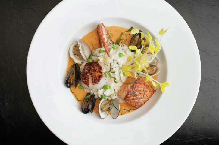 Seafood risotto with mussels, clams, scallop, shrimp, salmon and basil lobster sauce from La Table
