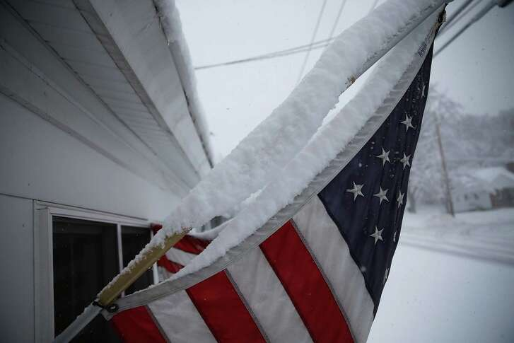 MANCHESTER, NH - FEBRUARY 05:  Snow is seen gathered on an American flag during a snow storm as primary voters make up their minds on a Presidential candidate on February 5, 2016 in Manchester, New Hampshire. Democratic and Republican Presidential are stumping for votes throughout New Hampshire leading up to the Presidential Primary on February 9th.