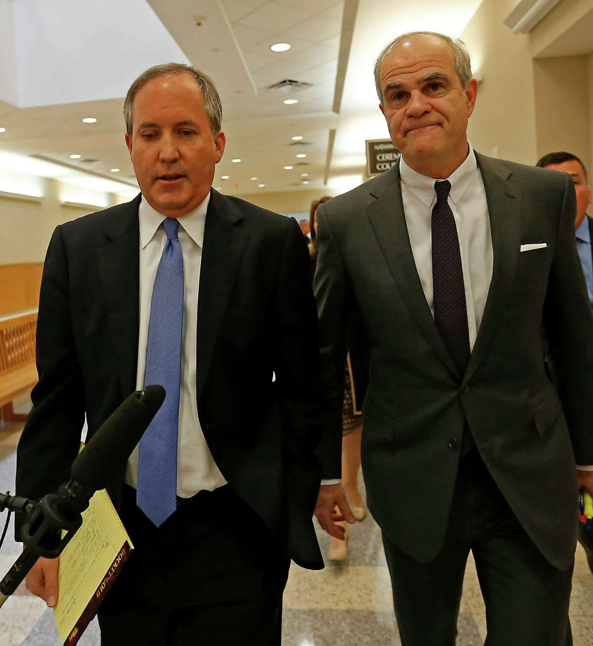 Texas Attorney General Ken Paxton, left, and his attorney Philip Hilder leave a courtroom after his pre-trial motion hearing at the Collin County courthouse. Paxton will not be able to use out-of-state contributions to pay his legal fees.