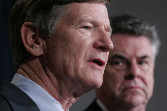 In this file photo, Rep. Lamar Smith, left, accompanied by Rep. Peter King, R-N.Y., right, speaks on Capitol Hill in Washington. He represents the interest of the 21st Congressional District well.