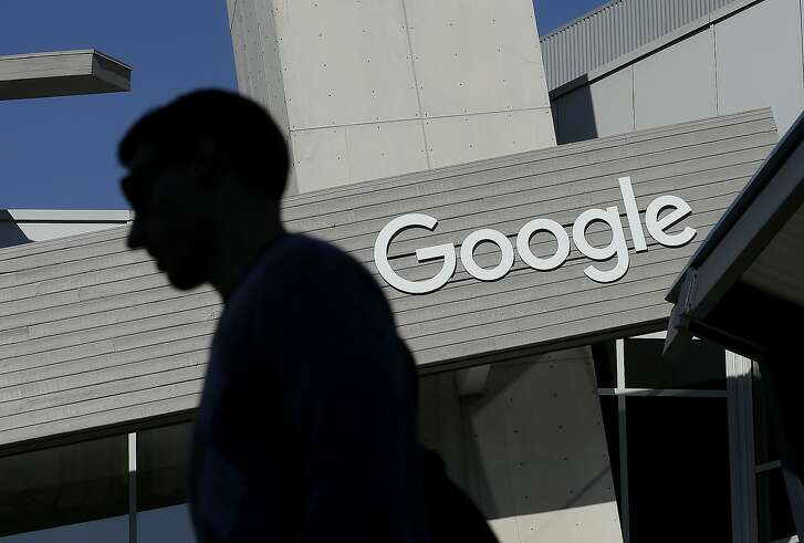 FILE - In this Nov. 12, 2015, file photo, a man walks past a building on the Google campus in Mountain View, Calif. Alphabet Inc., Google's holding company, reports financial results Monday, Feb. 1, 2016.  (AP Photo/Jeff Chiu, File)