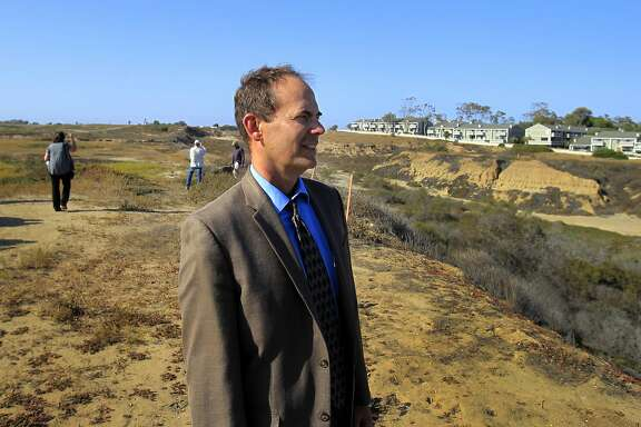 Coastal Commission Executive Director Charles Lester takes a tour at a proposed development project in Newport Beach, Calif., in a June 2014 file image. Members of the California Coastal Commission are moving to fire Lester, with a meeting scheduled for Feb. 10, 2016, the next step.