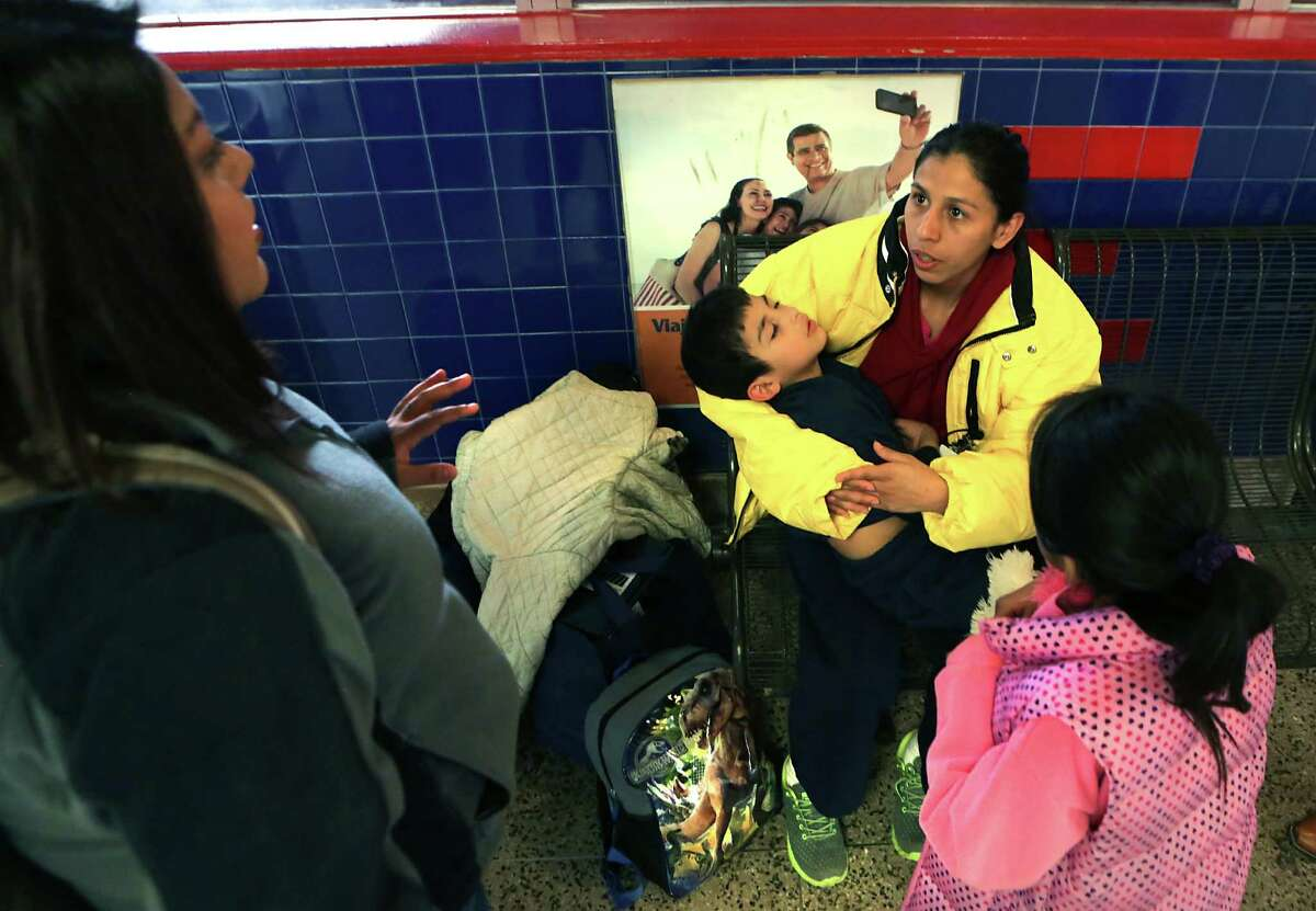 Susana Arevalo, 27 from El Salvador, sits with her two children Melany Arevalo 8, right, and Fernando Arevalo 6, in the bus station in San Antonio on Friday, Feb. 5, 2015, listening to Luz Varela, left, from the Mennonite house who was there to take them to stay overnight. Arevalo and her children were picked up recently in Atlanta during a raid by ICE and taken to the detention center in Dilley. She was released because of a medical condition.