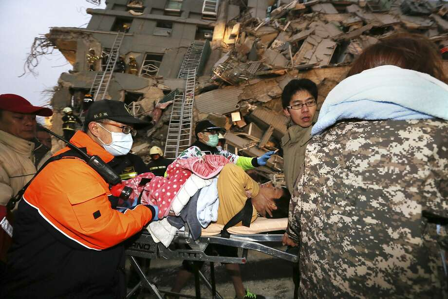 Rescue workers carry a man from a toppled building after an earthquake in Tainan, Taiwan. Photo: Associated Press