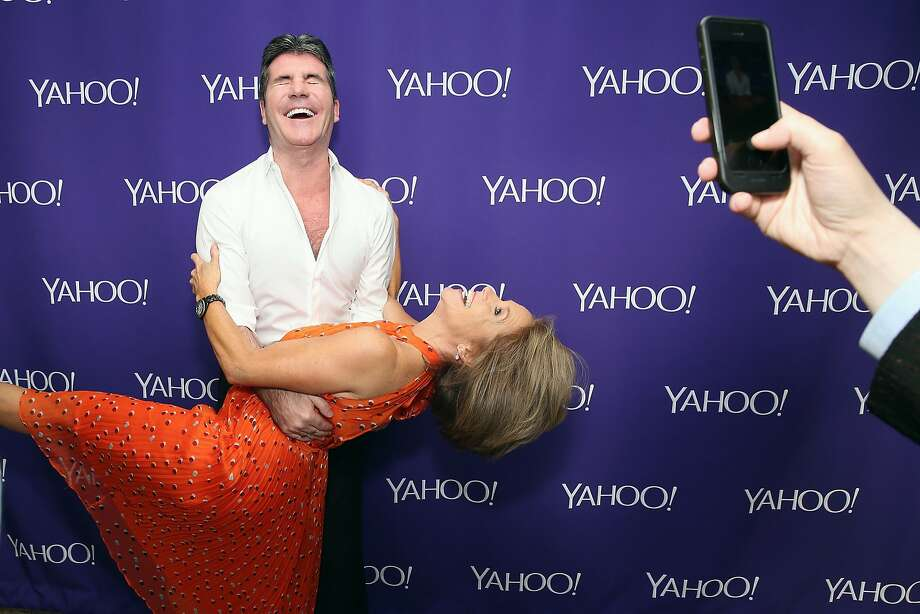 Katie Couric, who has a reported $10 million-a-year contract, appears with Simon Cowell at a 2015 Yahoo event. Photo: Cindy Ord