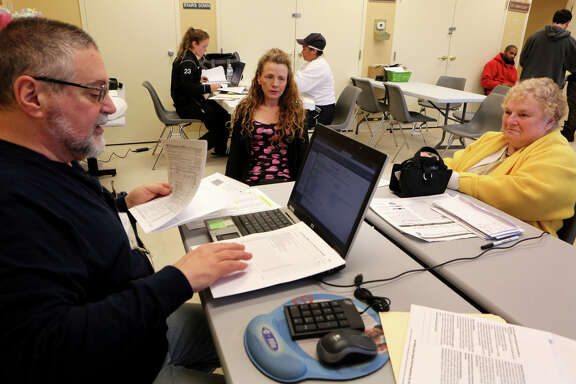 "Nick Tiberio (left), a retired CPA, prepares tax returns during last year's tax season for Alice Ellis (right), while her daughter, Renee Peterson, watches. New forms related to the health care law ""could potentially add one to three additional hours of preparation time to your return,"" according to one accountant."