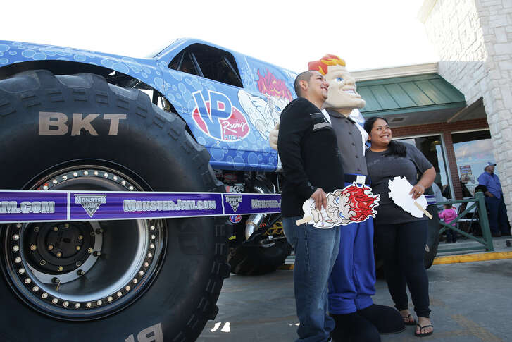 Jose Vega and Abigail Galvan pose for a picture with the mascot mad scientist as San Antonio based VP Racing Fuels promotes its products by showcasing its monster jam truck at their store location in McQueeney.
