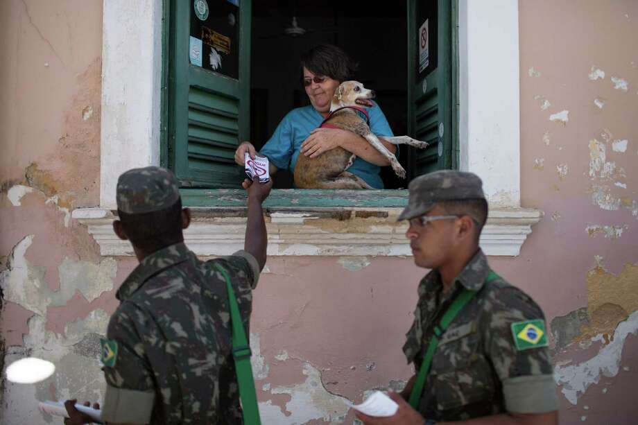 """Brazilian Army soldiers distribute flyers with information on how to combat the Aedes aegypti during the """"Burial of the Mosquito"""" carnival block parade in Olinda, Pernambuco state, Brazil, Friday, Feb. 5, 2016. The parade that happens every year during carnival inform residents and tourists about the dangers of the Aedes aegypti and teaches them how to combat the mosquitoes. (AP Photo/Felipe Dana) ORG XMIT: XFD107 Photo: Felipe Dana / AP"""