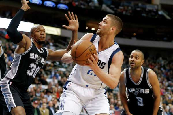 Dallas Mavericks forward Chandler Parsons (25) prepares to take a shot as San Antonio Spurs' David West (30) and Tony Parker (9) defend during the first half of an NBA basketball game, Friday, Feb. 5, 2016, in Dallas. (AP Photo/Jim Cowsert)