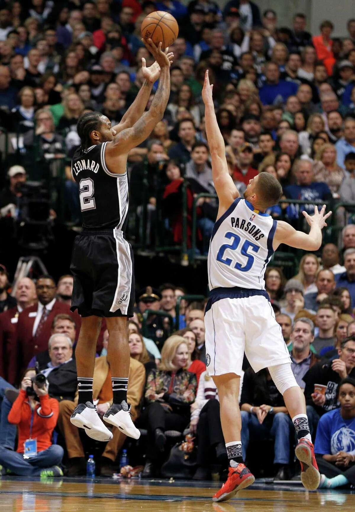 San Antonio Spurs forward Kawhi Leonard (2) shoots over Dallas Mavericks' Chandler Parsons (25) during the first half of an NBA basketball game Friday, Feb. 5, 2016, in Dallas. (AP Photo/Jim Cowsert)