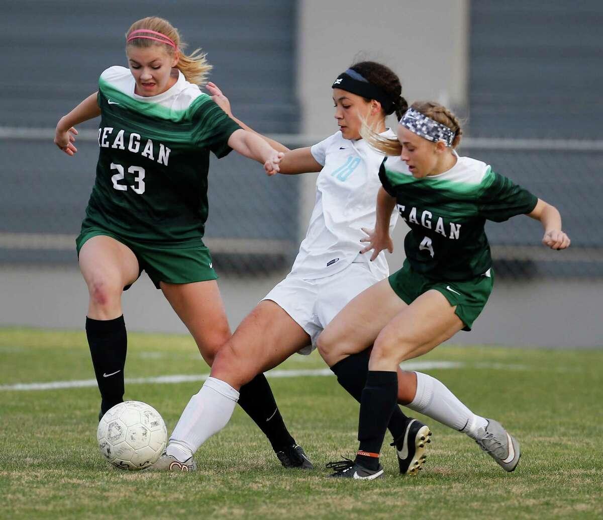 Johnson's Raquel Morris (18) splits Reagan defenders Lydia Jones (23) and Katy Johnson (04) in girls soccer at Blossom Soccer Stadium on Friday, Feb. 5, 2016. Johnson defeated Reagan, 2-1. (Kin Man Hui/San Antonio Express-News)