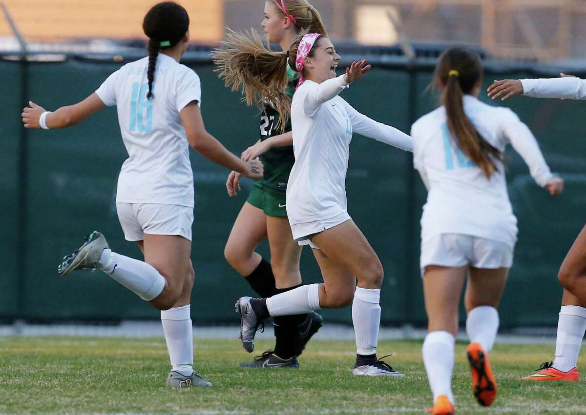 Johnson's Courtney Trimble (center) celebrates her penalty kick score with teammates against Reagan in girls soccer at Blossom Soccer Stadium on Feb. 5, 2016. Johnson defeated Reagan 2-1.