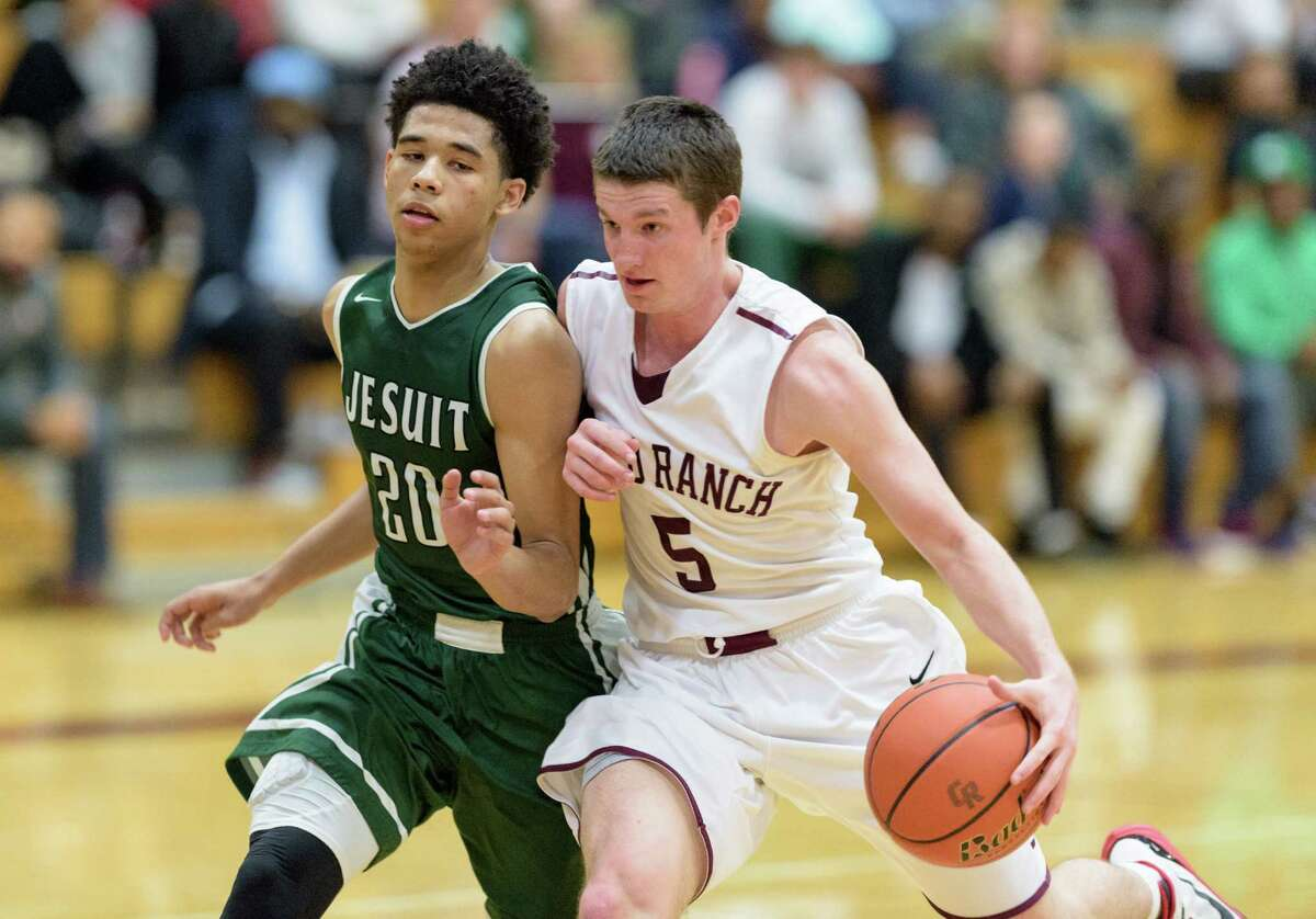 JR Adams (5) of the Cinco Ranch Cougars brings the ball up the court in the second half with Nate West (20) of the Strake Jesuit Crusaders defending in a high school basketball game on Friday, February 5, 2016 at the Cinco Ranch Cougars gym.