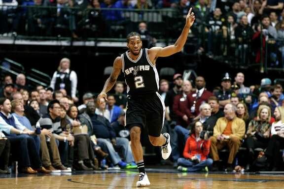 San Antonio Spurs forward Kawhi Leonard (2) celebrates sinking a basket against the Dallas Mavericks during the first half of an NBA basketball game, Friday, Feb. 5, 2016, in Dallas. (AP Photo/Jim Cowsert)
