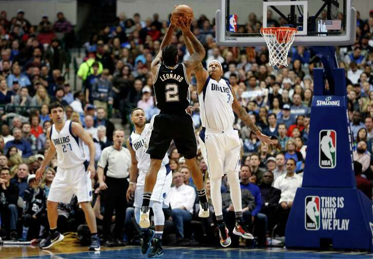 San Antonio Spurs forward Kawhi Leonard (2) goes up for a 3-point attempt as Dallas Mavericks' Charlie Villanueva (3) defends during the first half of an NBA basketball game, Friday, Feb. 5, 2016, in Dallas. (AP Photo/Jim Cowsert)