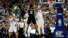San Antonio Spurs forward Kawhi Leonard (2) goes up for a 3-point attempt as Dallas Mavericks' Charlie Villanueva (3) defends during the first half of an NBA basketball game, Friday, Feb. 5, 2016, in Dallas. (AP Photo/Jim Cowsert)