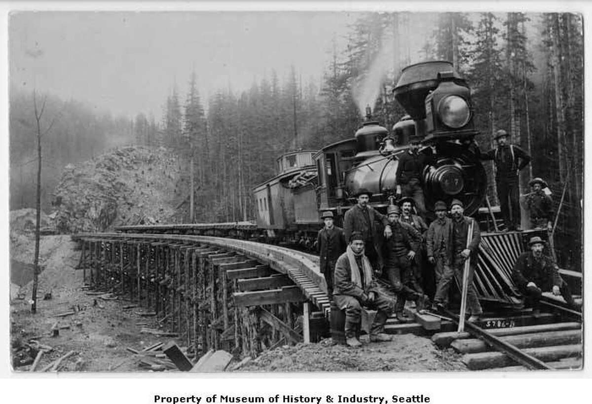 """""""In the 1880s, Chinese laborers were recruited by railroad companies because they worked for lower pay than whites. Chinese men were often assigned to such dangerous tasks as blasting through rock and laying tracks in tunnels or on river bluffs. Of the 20,000 men that built the Northern Pacific branch line between Pasco and Tacoma, 15,000 were Chinese. This 1885 photo shows a group of Northern Pacific Railroad construction workers in front of a locomotive at a crossing on the Green River. A Chinese worker sits in front, to the left, with a scarf around his neck."""" -MOHAI. Photo courtesy MOHAI, Seattle Historical Society Collection, image number shs5907."""