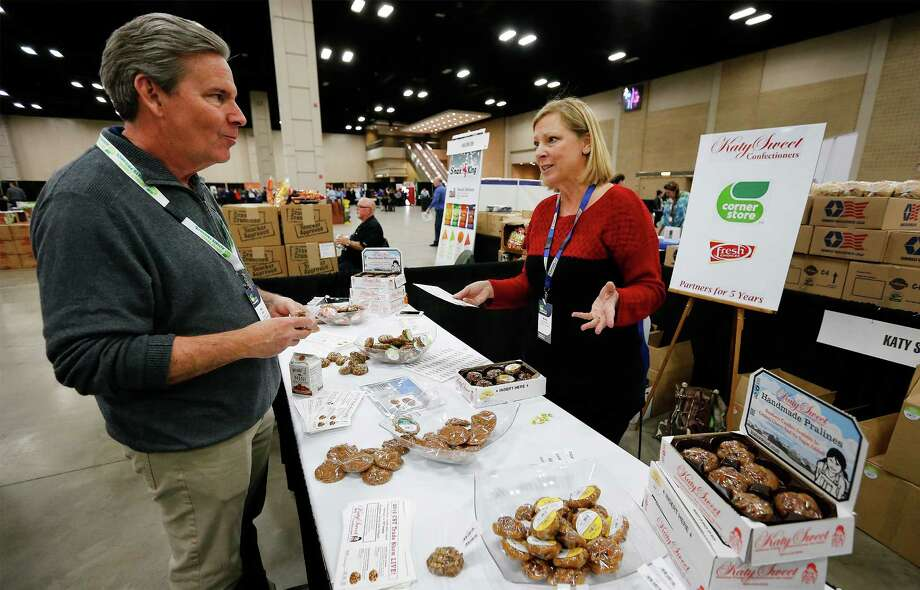 President of Operations at CST Brands Hal Adams (left) chats with Katy Sweet Confectioners' Gina Minzenmeyer as CST Brands holds in its annual convention for store managers at the Convention Center in San Antonio on Thursday, Feb. 4, 2016. Managers from 1,200 company-owned stores get to visit with about 100 suppliers to see a cross section of new products offered to CST to enhance sales in their stores. Katy Sweet has been doing business with CST Brands for five years according to Minzenmeyer. (Kin Man Hui/San Antonio Express-News) Photo: Kin Man Hui, Staff / ©2016 San Antonio Express-News