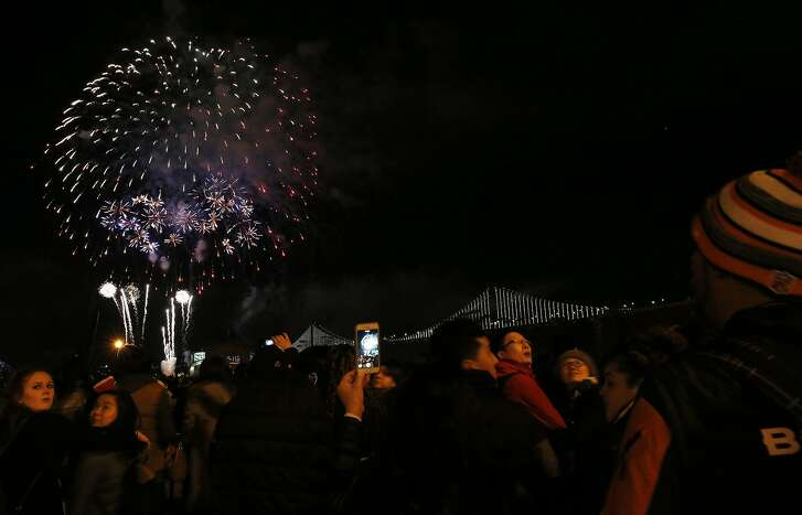 People watch and take photos during a fireworks show outside of Super Bowl City on Friday Feb. 5, 2016 in San Francisco, Calif.