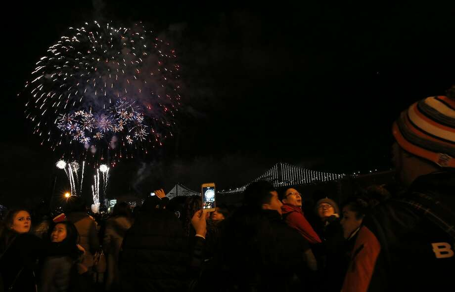People watch and take photos during a fireworks show outside of Super Bowl City on Friday Feb. 5, 2016 in San Francisco, Calif. Photo: Leah Millis, The Chronicle