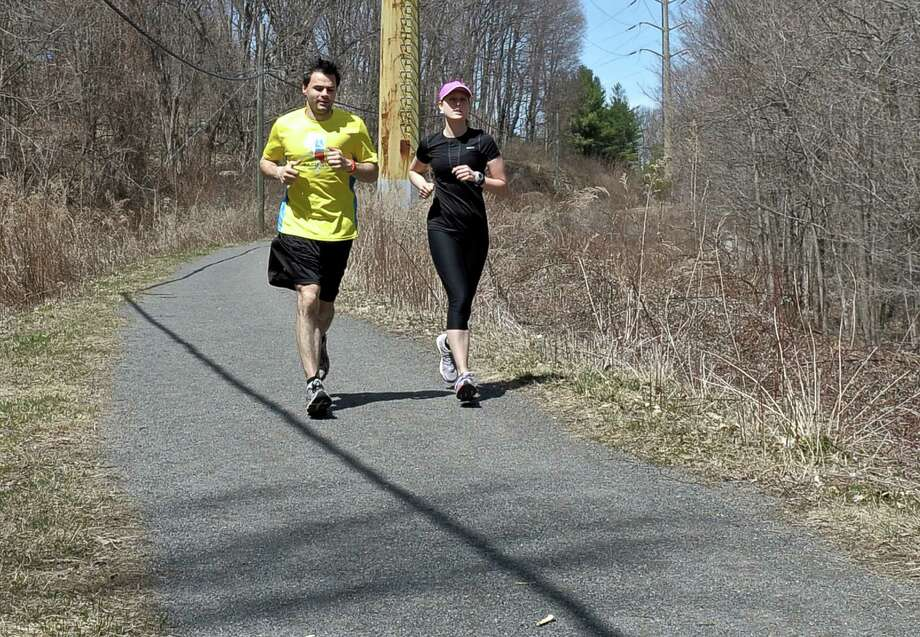 A pair of runner make their way along the Ridgefield Rail Trail which runs 2.3 miles from downtown Ridgefield to the Branchville area of the town. Wednesday, April 15, 2015, in Ridgefield, Conn. Photo: H John Voorhees III / H John Voorhees III / The News-Times
