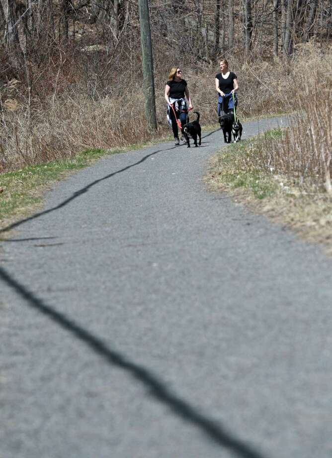 Karen Russo, left, and Jen Blair, both from Ridgefield, walk their dogs on the Ridgefield Rail Trail, which runs 2.3 miles from downtown Ridgefield to the Branchville area of the town. Wednesday, April 15, 2015, in Ridgefield, Conn. Photo: H John Voorhees III / H John Voorhees III / The News-Times