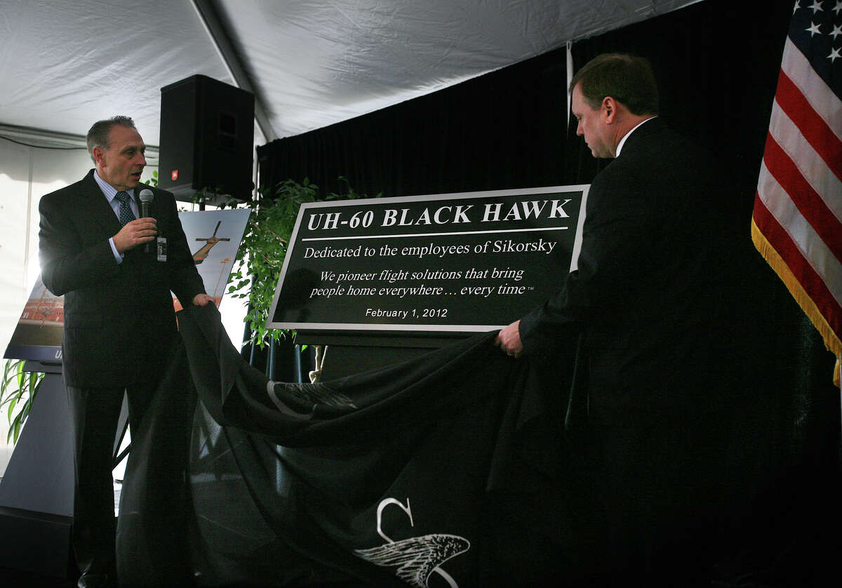 Jeff Pino, left, and Stratford, Conn. Mayor John Harkins unveil a plaque dedicating the Black Hawk helicopter on display in front of Sikorsky Aircraft's headquarters on February 1, 2012.
