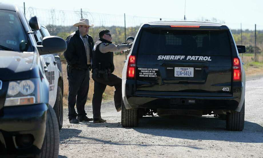 Uvalde County Sheriffs Deputies guard the intersection to a neighborhood several miles outside of Uvalde after a standoff resulted in multiple deaths on Saturday, Feb. 6, 2016. The incident started around 5 p.m. on Friday. Officials have not given an official account about the circumstances surrounding the standoff. Photo: Kin Man Hui, San Antonio Express-News / ©2016 San Antonio Express-News