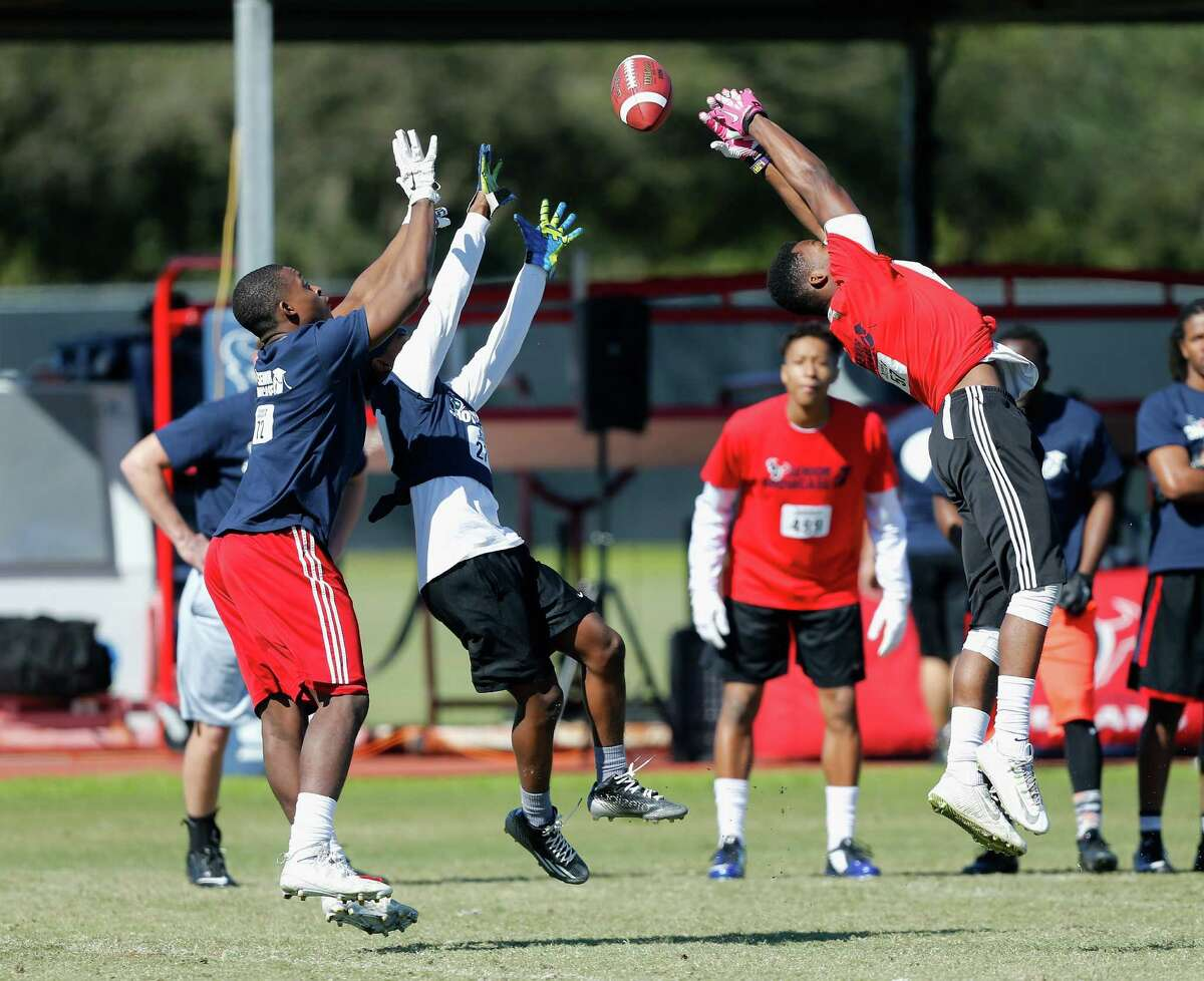 Wide receiver Derrick Arrington of Northland Christian has the ball go through his hands during drills as Rodnik Artmore of Ball high school, center, and Cordell Craft of Pickering High School looks to intercept at the Senior Showcase at the Houston Texans Methodist Training Center on Saturday, Feb. 6, 2016.