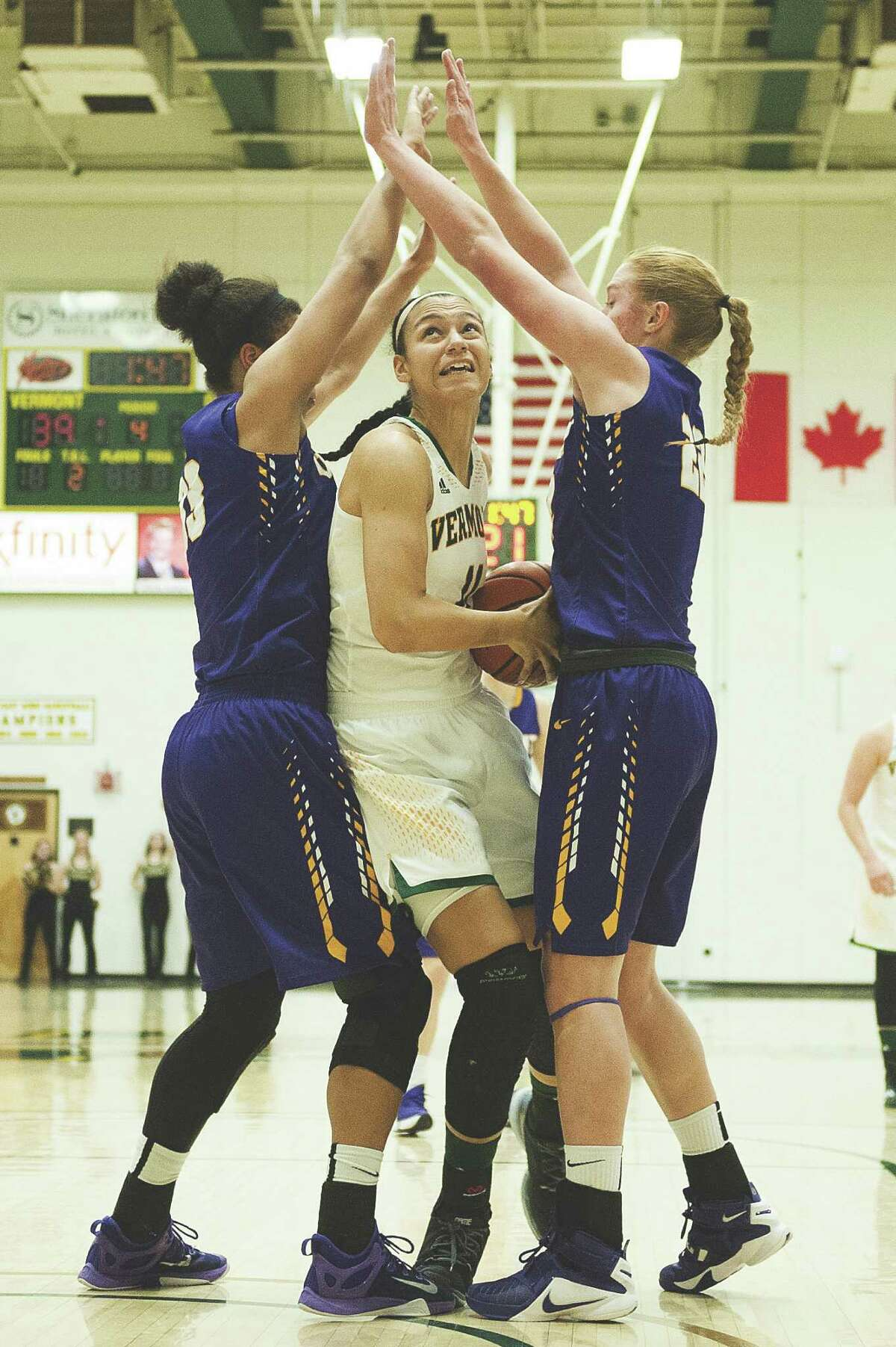 Vermont's Candice Wright (11) is guarded by Albany's Tiana-Jo Carter (33) and Heather Forster (22) during the women's basketball game between the Albany Great Danes and the Vermont Catamounts at Patrick Gym on Saturday afternoon February 6, 2016 in Burlington. (BRIAN JENKINS/for the FREE PRESS)
