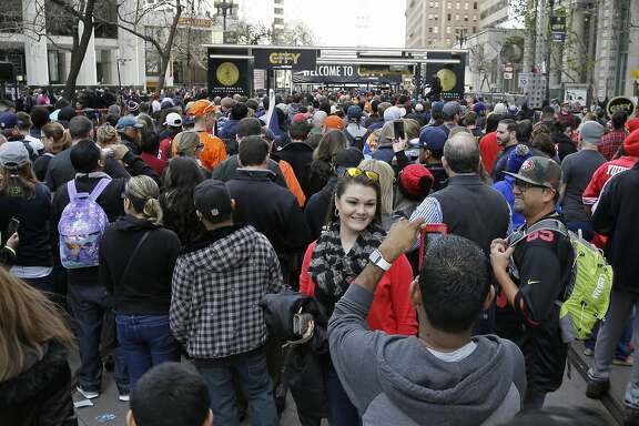 A woman has her picture taken as crowds jam Market Street to enter Super Bowl City Saturday, Feb. 6, 2016, in San Francisco. Long lines of people wrapped around blocks at several entrances to the free-to-the-public fan village designed to celebrate Super Bowl 50. (AP Photo/Eric Risberg)