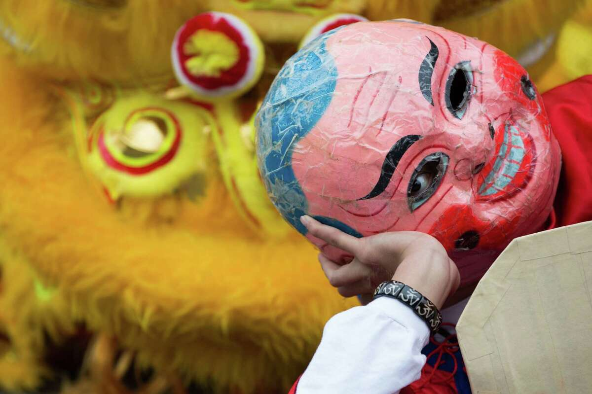 A dancer dressed as a monk lies in wait in front of the lions during the LQ Lion Dance group's performance in the Lunar New Year celebration at the Wing Luke Museum of the Asian Pacific American Experience in the International District on Saturday, Feb. 6, 2016.